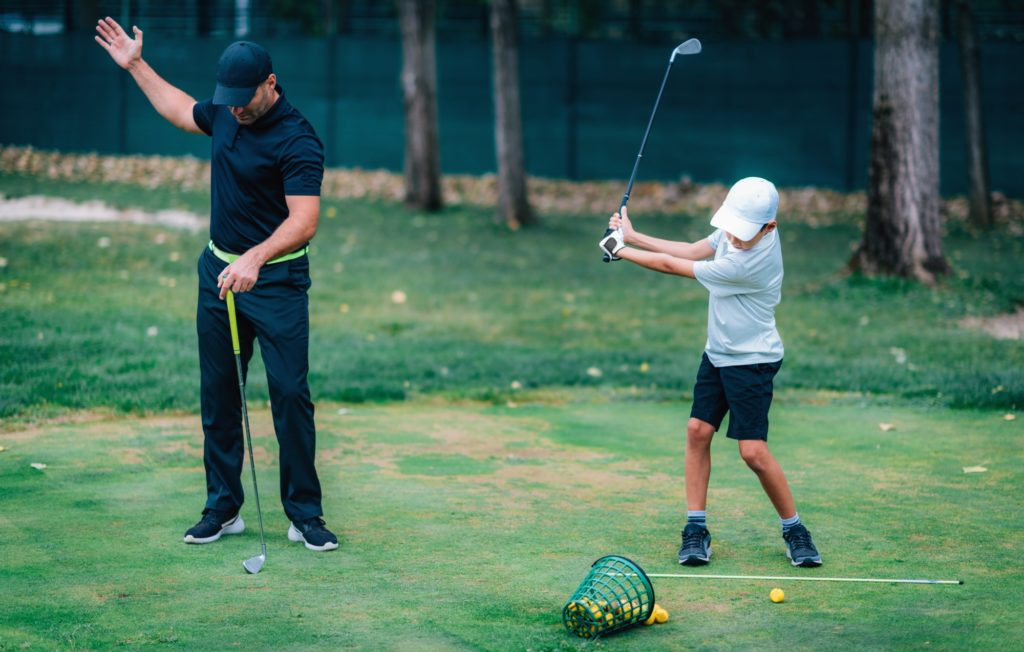 Golf Lesson. Golf Instructor Teaching Young Boy How to Swing