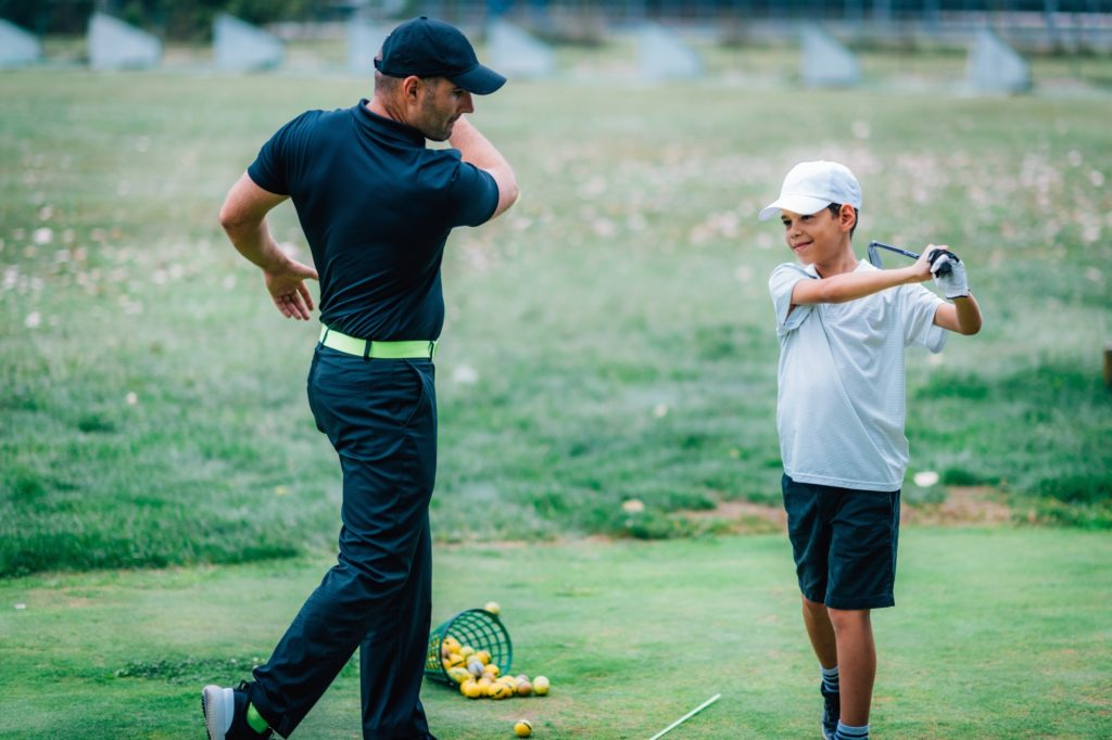 Golf Lessons. A golf Instructor and a boy practicing on a Golf Practice Range