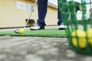 Low section of man playing golf at driving range